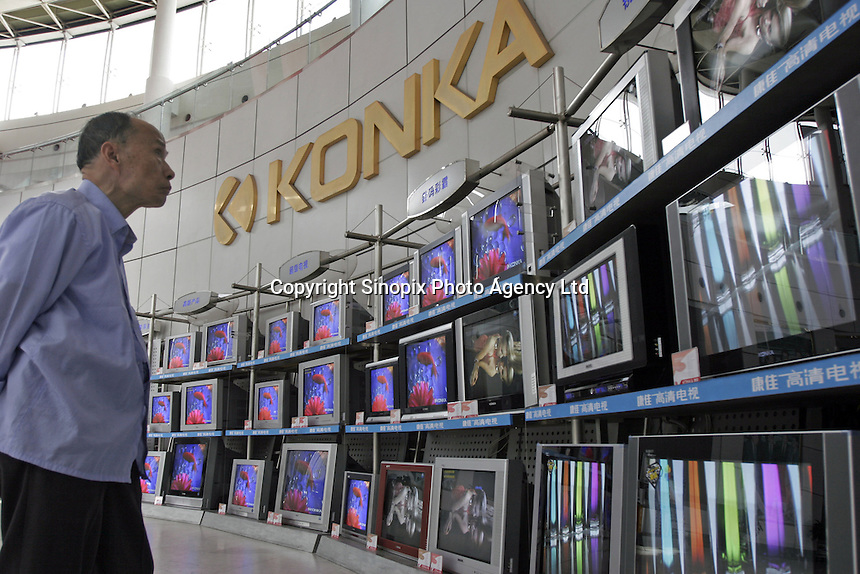 A man takes a close look of TV sets in the show room of Konka Group Co. Ltd. in Shenzhen, China. Konka is a Sino-foreign public share-hold enterprise, one of the China's 100 Best Electronic Enterprises, produces TV sets, mobile phones and home electric appliances..29 Mar 2005