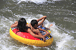 Boy and girl in inner tube in Confluence Park, Denver, Colorado, USA.