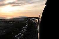 The Alaska Railroad's Coastal Classic train runs along Turnagain Arm into the setting sun.