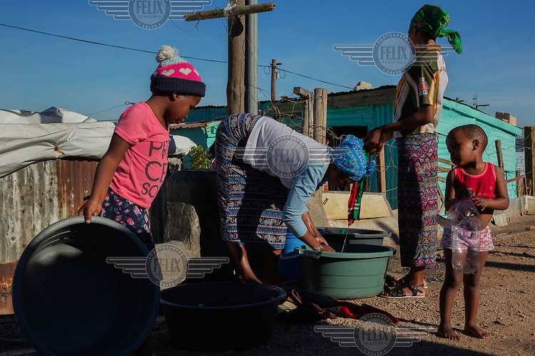 Women use a community tap to wash clothes in the township Station 11 in Villiersdorp, near Theewaterskloof reservoir. In early 2018, when the dam's water was predicted to decline to critically low levels, the city announced plans for 'Day Zero', when the municipal water supply would largely be shut off, potentially making Cape Town the first major city in world to run out of water. However, strict rationing staved off 'Zero Day' until the winter 2018 rainy season ended a three year drought and replenished the reservoir sufficiently to enable the city authorities to ease the water ration.