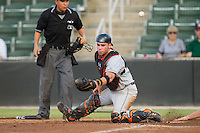 Delmarva Shorebirds catcher Austin Wynns (12) can't handle a throw at home plate as umpire Takahito Matsuda looks on during the game against the Kannapolis Intimidators at CMC-NorthEast Stadium on July 2, 2014 in Kannapolis, North Carolina.  The Intimidators defeated the Shorebirds 6-4. (Brian Westerholt/Four Seam Images)