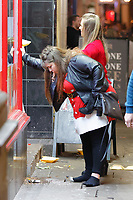 Pictured: A woman throws up outside a take-away restaurant. Friday 14 December 2018<br /> Re: Revellers in Wind Street, Swansea, Wales, UK.