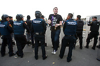 A USA fan walks through a line of Mexican police officers in riot gear that formed a perimeter around the bus of USA fans before USA vs. Mexico World Cup Qualifier at Azteca stadium in Mexico City, Mexico on March 26, 2013.