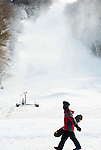 NEW HARTFORD,  CT-122616JS02-- A snowboarder walks past one of the hills as the snow guns coated the area Monday at Ski Sundown in New Hartford. The hills opened for the season this past Friday. <br />   Jim Shannon Republican American