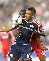 New England Revolution midfielder Juan Agudelo (10) attempts to control the ball as Chicago Fire defender Bakary Soumare (4) closely defends. In a Major League Soccer (MLS) match, the New England Revolution (blue) defeated Chicago Fire (red), 2-0, at Gillette Stadium on August 17, 2013.