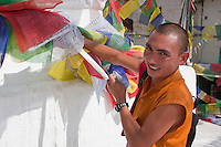 Bodhnath, Nepal.   Buddhist Monk Adjusts the Prayer Flags Decorating the Bodhnath Stupa.     The five colors represent the five elements: space, water, fire, air, and earth.