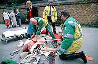 Paramedic uses the paddles of a defib to shock the victim of a heart attack the casualty also injured his head after falling over in the process of the heart attack. This image may only be used to portray the subject in a positive manner..©shoutpictures.com..john@shoutpictures.com