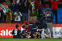 Michael Bradley (hidden) of USA is mobbed by teammates as they celebrate his equalising goal to make the score 2-2 against Slovenia