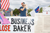 """A man identified as Sam or Samson sings """"I'm Proud to be an American"""" as people gather for an anti-lockdown protest organized by the alt-right group Super Happy Fun America near the home of Massachusetts governor Charlie Baker in Swampscott, Massachusetts, on Sat., May 16, 2020. The protest was in defiance of Massachusetts orders mandating face coverings and social distancing and prohibiting gatherings larger than 10 people during the ongoing Coronavirus (COVID-19) global pandemic. The state's stay-at-home order is expected to be updated on May 18, 2020, with a phased reopening plan issued by the governor as COVID-19 cases continue to decrease. Anti-lockdown protests such as this have become a conservative cause and have been celebrated by US president Donald Trump. Many of the protestors displayed pro-Trump messages or wore Trump campaign hats and shirts with phrases including """"Trump 2020"""" and """"Keep America Great."""" Super Happy Fun America, organizers of the protest, are an alt-right organization best known for creating the 2019 Boston Straight Pride Parade."""