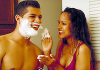 Young ethnic playful couple frolicking in the bathroom while he shaves. Young ethnic couple. Houston Texas USA.