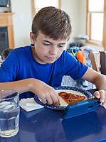 Thirteen-year-old Boy Watching Video Game during Lunch.  Avon, Outer Banks, North Carolina.