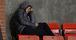 A member of Liverpool Women Team watches the play from the top of the stand