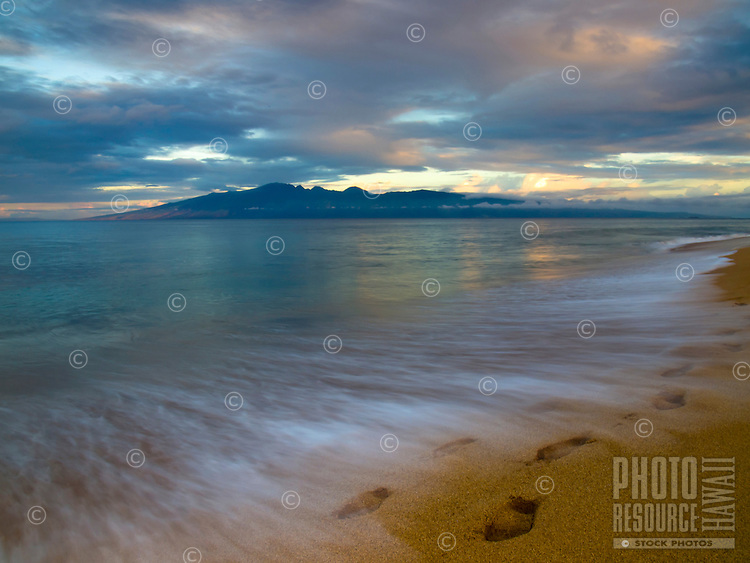 At sunrise, waves slowly wash away footprints in the sand along the shoreline at Ka'anapali Beach, Maui, with Moloka'i in the distance.