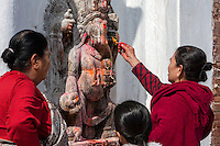 Nepal, Patan.  Women Making Offerings at Neighborhood Shrine to Ganesh.