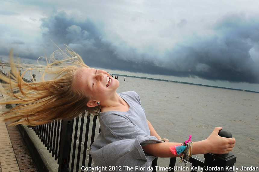 Kelly.Jordan@jacksonville.com--052812--Winnie Pajcic, 9, of Jacksonville holds on to the railing as she leans back and lets the wind blow through her hair as she and her family visited Stockton Park in Ortega to view watch the weather as North Florida residents deal with the aftermath of Tropical Storm Beryl moves ashore near Jacksonville Beach overnight Monday May 28, 2012. Winnie's mom said it is a family tradition to drive around after storms to get a perspective of how it affected their neighborood.(The Florida Times-Union, Kelly Jordan)
