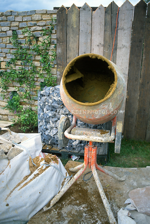 Cement mixer in backyard garden, building patio and hardscaping