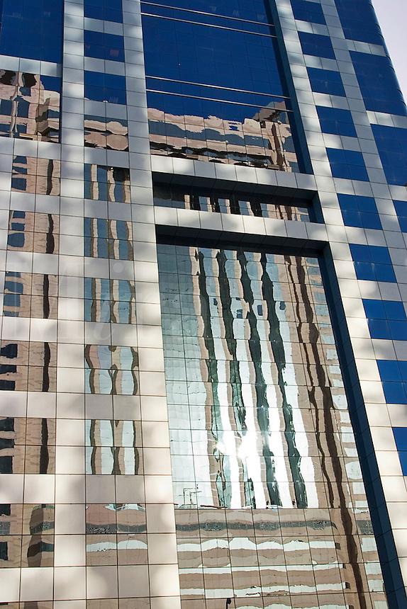 Dubai, United Arab Emirates. Reflections in the faade of modern glass clad building. Abu Dhabi Road..