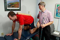 UVA SPEED Clinic director Max Prokopy, right, uses the straight edge of a 2x4 on Matt Clay to show proper positioning when stretching during a visit to the clinic in Charlottesville, VA. Photo/Andrew Shurtleff