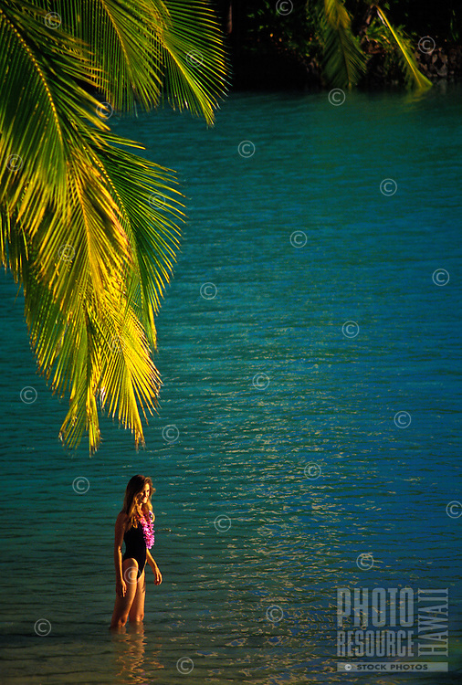 Woman standing on blue water wearing an orchid lei at the Hilton lagoon, surrounded by palm frons, Waikiki