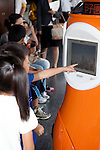 """August 01 2012, Tokyo, Japan - A kid touches the new robot guide """"Tawabo"""" at Tokyo Tower. Tokyo Tower implemented the new robot guide which name is """"Tawabo"""", the first indoor robot guide in Japan. It can speak Japanese, English, Chinese and Korean, it weights 200kg and it is 160cm tall."""
