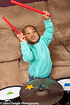 Two year old toddler boy playing musical instrument drum set holding sticks high and hitting them together