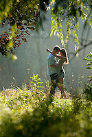 Young couple embracing in field underneath trees