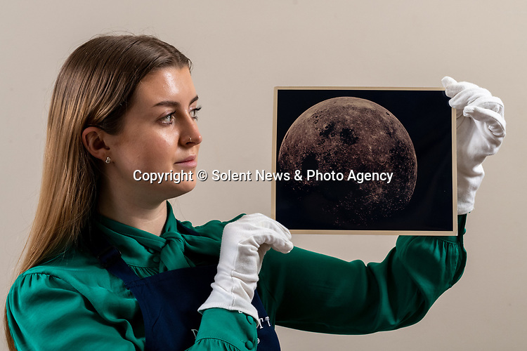 Pictured: Sales Coordinator Lulu Randall  holds up  an original print of the near-full moon as witnessed by the Apollo 8 crew during homebound journey with an etimated value of £1,000-£2,000 ahead of auction today [WEDNESDAY] at Dreweatts Auction House in Newbury, Berks.<br /> <br /> The near-full moon was captured in all of its' glory during the Apollo 8 crew's homeward journey. Just after the trans-earth injection the crew were afforded the opportunity to view different aspects of the moon never visible to terrestrial viewers.<br /> <br /> Some of the most historic photographs chronicling the history of man's exploration of space, from early expeditions, to some of the latter trips of the 1990s will be sold at auction.  Over 600 images, many of which capture historic moments, such as the first humans in space, the first spacewalk and the first moon landing will be auctioned today on March 17th 2021 as part of the Space Exploration Photography and Ephemera auction by Dreweatts.<br /> <br /> © Jordan Pettitt/Solent News & Photo Agency<br /> UK +44 (0) 2380 458800