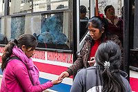 Peru, Cusco.  Woman in Pink Collecting Fare from Disembarking Bus Passenger.