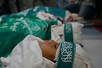 """Mourners gather around the bodies of four Palestinian children and their mother from Abu Maateq family during their funeral in Beit Lahia in the northern Gaza Strip on April 28, 2008. Four children, aged one to five, their mother and a militant were killed in Israeli operations in Gaza today as Palestinian factions headed to Egypt for talks on a possible truce. The four siblings -- aged one, three, four and five -- were killed when a tank shell hit their home in the town of Beit Hanun, and their mother died later of her wounds, doctors at the Kamal Radwan hospital said.""""photo by Fady Adwan"""""""