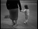 A grandmother helps her granddaughter cross a busy street, Prague, Czech Republic.