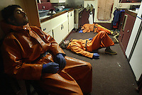 "10/20/03 crab NWS::  Crewmen on the F/V Exito from left to right back: Erik Synder, Lee Fleury, and Jeff Madigan, all from Skykomish, Wash., crash on the galley floor during a short break inbetween picking up strings of gear.  (Crab pots are laid out in ""strings"" forming a line on the ocean floor for 20 to 35 pots.)  They had worked almost 24 hours straight getting only a few breaks for a quick meal and naps, such as this one.  Shortly afterwards they got 3 hours of sleep before having to return to deck.  The current crab rationalization and buyback program, now being considered in congress, would eliminate the need for round-the-clock fishing and potentially make the industry safer, but would place crab quotas in the hands of processing companies, something many crab fishermen are against.  This year's ADFG forecast of 14.7 million pounds was the largest projected harvest of Bristol Bay red king crab in 12 years.  It will be several weeks before crabbers know if that harvest was met.  The season lasted 5 days and 2 hours and was plagued with gale force winds of 35 knots or higher almost everyday."