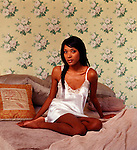 African American woman relaxing on bed looking at camera