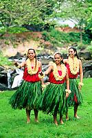 Three hula dancers near Waterfall in ti leaf skirts and yellow plumeria leis