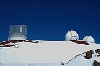 Two snow boarders stand on the ridge between the Subaru and W.M. Keck Observatories Mauna Kea The Big Island of Hawaii