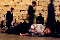 A Jewish man sleeps in front of the Western Wall as others pray or sleep July 18,2002 in Jerusalem's Old City. The Jewish people pray and fast in memory of two Jewish temples destroyed thousands of years ago. As part of the Jewish tradition people spend the night at the Western Wall, the only remain of the second temple, Jews believe, praying or sleeping as a symbol of mourning the destruction.