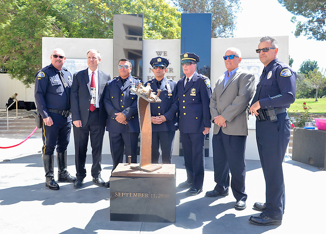 (left to right) Huntington Beach police officer, Corwin Bales, Mayor Jim Katapodis, NY Port Authority officer, Vincent Zappulla, Jr., New York Port Authority Detective Frank Accardi, Port Authority Captain Kevin Devlin, Port Authority officer, Robert Egbert and Huntington Beach officer, Jack Paholski stand in front of the new 9/11 Memorial located at Huntington Beach city hall.<br /> <br /> ///ADDITIONAL INFORMATION: hb.0915.memorial – 9/11/16 – MICHAEL KITADA, ORANGE COUNTY REGISTER - _DSC8518.jpg - <br /> Summary: The Huntington Beach Police Officers' Foundation's 9-11 Memorial Committee unveils a $200,000 monument including steel from the toppled World Trade Center, at City Hall. The event will include music, a flyover, New York police and others with connections to the 9-11 rescue and victims of the tragedy.