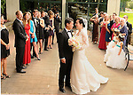 A multi-cultural bride and groom, Latin American and Asian, greet each other with their family and friends witnessing the special moment.