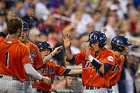 Cal State Fullerton Titans catcher A.J. Kennedy (10) is sprayed with water after scoring during the NCAA College baseball World Series against the Vanderbilt Commodores on June 14, 2015 at TD Ameritrade Park in Omaha, Nebraska. The Titans were leading 3-0 in the bottom of the sixth inning when the game was suspended by rain. (Andrew Woolley/Four Seam Images)