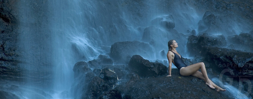 A Girl relaxing under the biggest waterfall in Palau, Micronesia during the wet season.