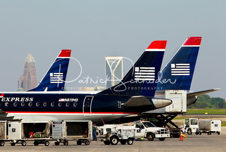 Cargo carts shuttle luggage around as US Airways express jets sit at the gates, with the Charlotte skyline in the background, at Charlotte-Douglas International Airport in Charlotte, North Carolina. Charlotte-based photographer has other images of transportation, airplanes on runways (and taking off and landing) and interior/exterior airport images of Charlotte-Douglas Intl Airport in portfolio.