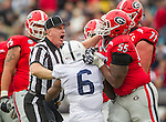 The referee breaks up a fight between Penn State running back Andre Robinson and Georgia's Dyshon Sims (55) and John Theus (71) in the first half of the TaxSlayer Bowl NCAA college football game in Jacksonville, Fla., Saturday, Jan. 2,  2016. Georgia defeated Penn state 24-17.  (AP Photo/Mark Wallheiser)