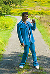 Man in blue leisure suit posing to camera