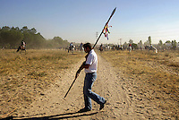 A man with a lance walks to his position on the plain as he awaits the arrival of the bull during the 'El toro de la Vega' (The bull of the plain) bullfight, 13 September 2005 in Tordesillas. On the second Tuesday of September, since the fifteenth century the village has celebrated this very special bullfight. The arena of the bullfight is the plain across the river from the village and it is up to a number of young men with lances to dispute the honour of making the fatal strike. (c) Pedro ARMESTRE