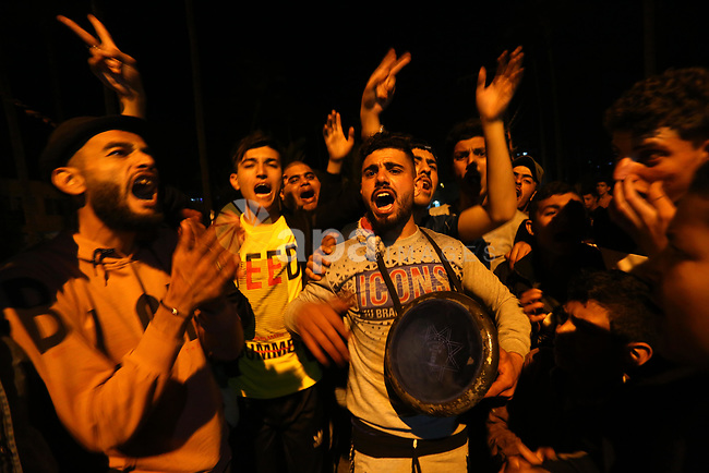 Palestinians chant slogans as they burn tires during a rally in support of the Al-Aqsa Mosque, in Deir al-Balah, in the center of Gaza strip on April 25, 2021. There have been nightly disturbances since the start of the Muslim holy month of Ramadan on April 13, amid Palestinian anger over police blocking off access to the promenade around the walls of the Old City and a ban on gatherings. Photo by Ashraf Amra