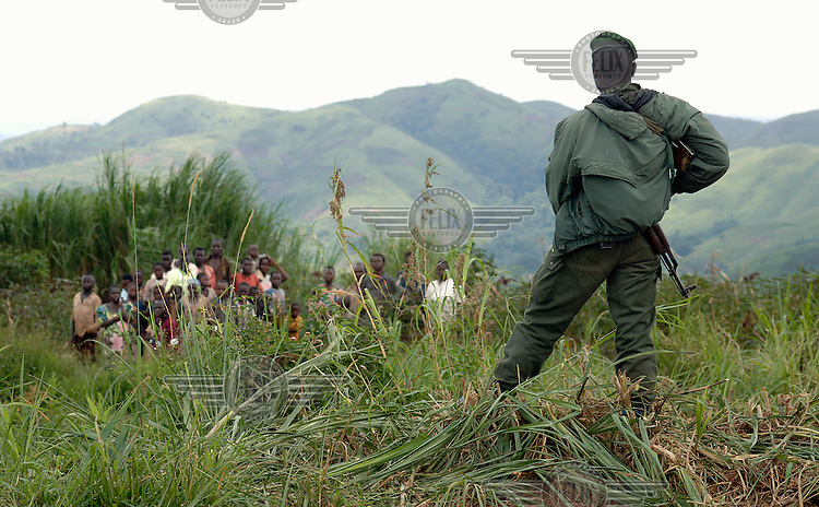 A Congolese soldier with a machine gun keeps civilians at a distance.  He has been trained by MONUC (United Nations Mission in the Democratic Republic of Congo), a United Nations (UN) peacekeeping mission..