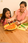 8 year old girl in kitchen with mother shown how to peel vegetables carrots chores cooking
