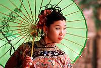 A portrait of a young Chinese woman in traditional attire holding a parasol. Xian, China.