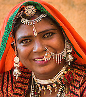 Portrait of woman at the entrance of the fort  wearing and selling traditional Rajasthani jewellery.  Jaisalmer, Rajasthan, India.