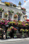 Great Britain, England, London: Colourful pub with hanging baskets of flowers in Summer