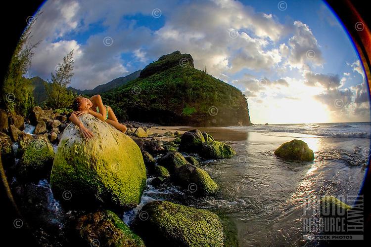A woman reclines on an algae-covered boulder at Hanakapi'ai Stream and Beach, Na Pali Coast, Kaua'i.